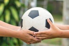 Kid's-Hände, die alten Fußball halten lizenzfreie stockfotos