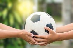 Kid's-Hände, die alten Fußball halten lizenzfreie stockfotografie