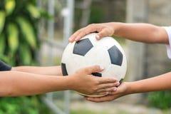 Kid's-Hände, die alten Fußball halten stockbilder
