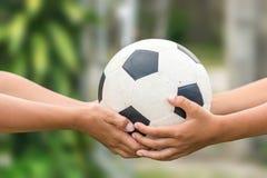 Kid'shanden die oude voetbal houden royalty-vrije stock afbeeldingen
