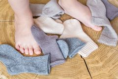 Kid& x27; 在逗人喜爱的小另外色的开士米堆的s腿编织了在木书桌背景的新出生的婴孩袜子 库存图片