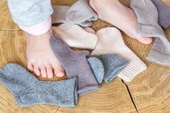 Kid& x27; 在逗人喜爱的小另外色的开士米堆的s腿编织了在木书桌背景的新出生的婴孩袜子 免版税库存照片