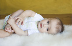 Kid. The little boy lies on a fur rug Stock Images
