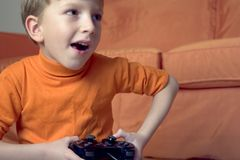 Kid. Playing video-game, concept of excitement and action Stock Photography