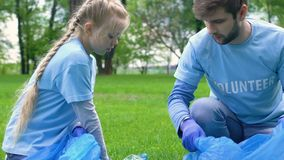 Kid and adult volunteers picking litter in park giving high-five, love to nature. Stock footage stock footage