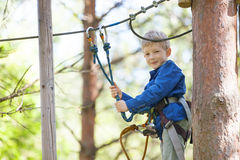 Kid at adventure park. Brave little boy enjoying treetop adventure park Royalty Free Stock Image