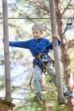 Kid at adventure park. Brave little boy enjoying treetop adventure park Stock Images
