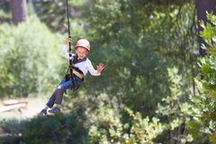 Kid at adventure park. Brave little boy ziplining in adventure park Royalty Free Stock Photos