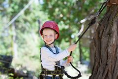 Kid in adventure park. Happy kid climbing at adventure park Royalty Free Stock Photos