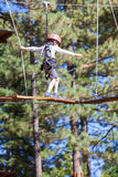 Kid in adventure park. Little boy being active at treetop adventure park Royalty Free Stock Photos