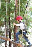 Kid in adventure park. Little boy climbing at adventure park alone Royalty Free Stock Photos