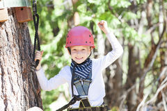 Kid in adventure park. Positive little boy feeling happy after climbing at treetop adventure park Royalty Free Stock Photography
