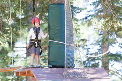 Kid at adventure park. Positive little boy at outdoor treetop adventure park being active and healthy Stock Images