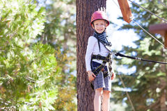 Kid at adventure park. Positive little boy at outdoor treetop adventure park being active and healthy Royalty Free Stock Photos
