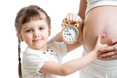Kid with an alarm clock and pregnant woman belly Stock Photo
