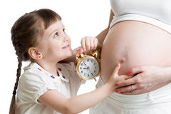 Kid with an alarm clock and pregnant woman stomach Stock Photography