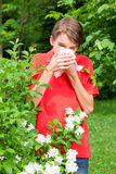 Kid with allergic rhinitis in a spring garden. Teenage boy with hay fever blowing his nose allergic to bloom flowers in a spring garden Royalty Free Stock Image
