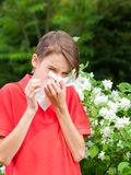 Kid with allergic rhinitis in a spring garden. Teenage boy with hay fever blowing his nose allergic to bloom flowers in a spring garden Stock Images