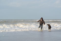 Kid And Dog Having Fun In The Waves Stock Photos