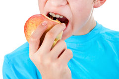 Kid with the Apple. Teenager eat an Apple Isolated on the White Background Stock Image