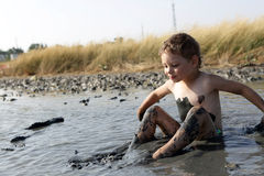 Kid applying black healing clay. In Primorsko-Akhtarsk, Russia royalty free stock image