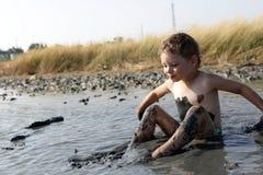 Kid applying black healing clay Royalty Free Stock Image