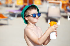Kid applying sunscreen spray Stock Images