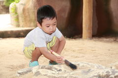 Kid Archeology. A Asia boy discovery of a dinosaur bone buried in the sand at the Singapore Jurong Bird Park Royalty Free Stock Photography