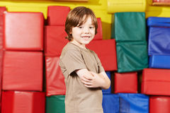 Kid with arms crossed in gym. Happy kid with his arms crossed standing in gym of kindergarten Royalty Free Stock Images