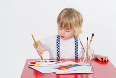 Kid and art education. Cute toddler drawing with colorful water painting Stock Photos