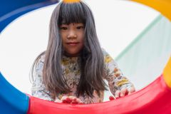 Kid asian girl having fun to play on children`s climbing toy at royalty free stock photo