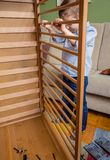 Kid assembling cot for a newborn at home. Portrait of cute kid assembling cot for a newborn at home. Family leisure concept Stock Images