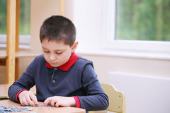Kid assembling puzzles. Little kid assembling puzzles indoors Stock Photo