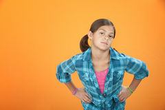 Kid Attitude. Young girl on orange background with hands on hips Stock Photography