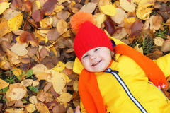 Kid in autumn laying in leaves Royalty Free Stock Images