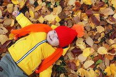 Kid in autumn laying in leaves Stock Images