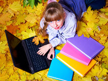 Kid in autumn orange leaves with laptop. Royalty Free Stock Photos