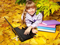 Kid in autumn orange leaves with laptop. Royalty Free Stock Photo