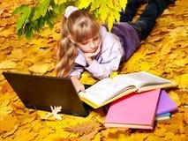 Kid in autumn orange leaves with laptop. Stock Photo