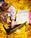 Kid in autumn orange leaves with laptop. Stock Images