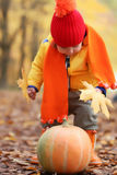 Kid in autumn park with pumpkin Royalty Free Stock Photos