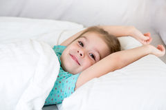 Kid awaked up in her bed Royalty Free Stock Photos