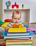 Kid baby boy lying on floor and read book. Royalty Free Stock Photos