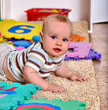 Kid baby boy plying with puzzle toy on floor Royalty Free Stock Image