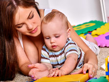 Kid baby boy plying with puzzle toy on floor Stock Image