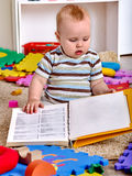 Kid baby boy sitting on floor and reading book Stock Photos