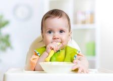 Kid baby eating food on kitchen Stock Photos