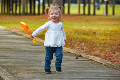 Kid baby girl with toy guitar walking in park Royalty Free Stock Photography