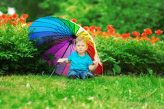 Kid, baby with rainbow umbrella in park. A child on a background Stock Photos