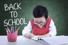 Kid back to school and make a picture in class Royalty Free Stock Images